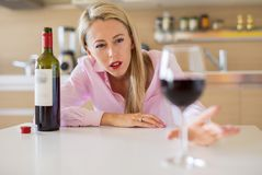 Woman reaching for a glass of wine while alone at home. Middle aged woman reaching for a glass of wine while alone at home stock images