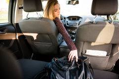 Woman reaching handbag from back seat Royalty Free Stock Photo