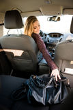 Woman reaching handbag from back seat Royalty Free Stock Images
