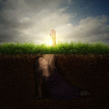 Woman reaching for help. A woman buried under ground reaching out for help Stock Images