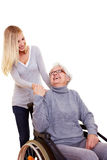 Woman reaching out to handicapped. Young woman reaching out to an elderly handicapped woman Stock Image