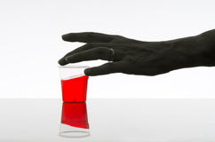 Woman reaching for red drink. Alcohol, addiction concept. Dark. Stock Photography