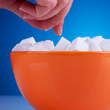 Woman reaching for some sugar cubes Stock Photo