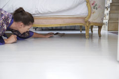 Woman Reaching Towards Slippers Under Bed Royalty Free Stock Photography
