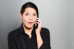 Woman reacting in amazement to news on her mobile Stock Photography