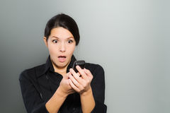 Woman reacting in amazement to news on her mobile Royalty Free Stock Photos