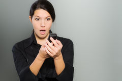 Woman reacting in amazement to news on her mobile Royalty Free Stock Image