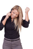 Woman reacting in jubilation to a call. On her mobile phone grinning broadly and raising her fist in the air in triumph at a successful outcome, studio portrait royalty free stock photos