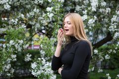 Woman reacts with asthma on hay fever while being in park royalty free stock photo