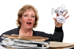 Woman reacts to tossing paper. Mature woman tossing away balled up paper royalty free stock photo