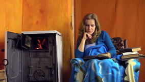 Woman read book at home near warm stove fire place on winter day stock video footage