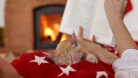 Woman read a book lying on sofa at the fireplace stock video footage