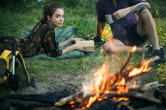 Woman read book and man with mug at campfire. Woman read book and men with mug at campfire. Couple of hikers relax at bonfire on nature. Summer vacation concept stock photos