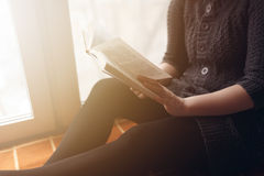 Woman read book seat on the plaid near window Royalty Free Stock Images