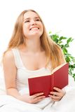Woman read book sitting in bed. And laughing Royalty Free Stock Photography
