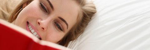 Woman read book stay in bed. Young blond pretty woman read book stay in bed Stock Photography