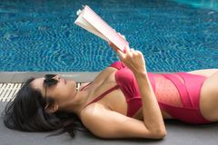 Woman read book at swimming pool. Asian beautiful tan woman in red one piece swimsuit lie down and read book near swimming pool. Thai female relax in summer royalty free stock images