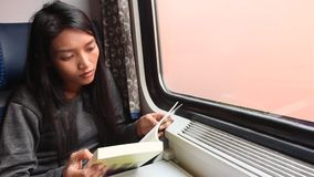 Woman read her book while traveling by train. Young Asian woman read her book while traveling by train stock video