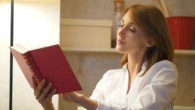 Woman read vintage book at home. Woman read red vintage book at home alone. Cozy home evening concept stock footage