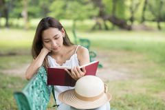 Woman read text in garden. Portrait of Asian beautiful brunette woman read text book and sit on garden chair with greenery and nature fresh air background. Cute Royalty Free Stock Image