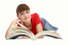 A woman reading. A beautiful woman reading a book on a floor isolated on a white background royalty free stock image