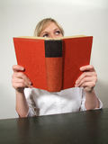 Woman reading. A blond haired woman sitting at a table, looking up from reading a thick book with a red hardbound cover Royalty Free Stock Photos