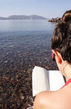 Woman reading. A book siting near the sea Royalty Free Stock Images