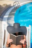 Woman Reading A Book By The Pool Royalty Free Stock Images