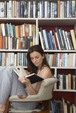Woman Reading Against Bookshelves Stock Photography