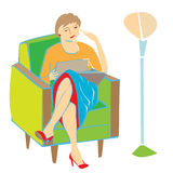 Woman reading on armchair Royalty Free Stock Image