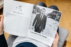 Woman reading article in M le magazine du monde
