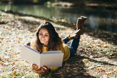 Woman reading in autumn outdoor royalty free stock photos