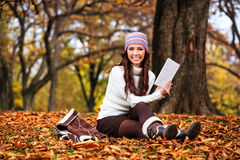 Woman reading in autumn park Stock Photo