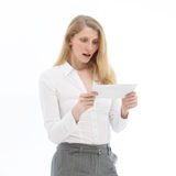 Woman reading bad news. Attractive blonde businesswoman reacting in shock and disbelief on reading bad news Royalty Free Stock Image