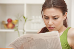 Woman reading bad news in newspaper Royalty Free Stock Image