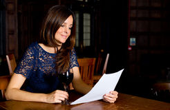 Woman reading in a bar Stock Image