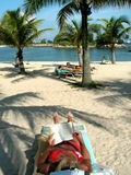 Woman reading on beach. Relaxation at its best. Reading in the shade by the seaside Stock Photography