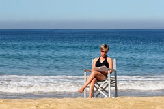 Woman reading on the beach Royalty Free Stock Photos