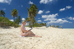 Woman reading on beach. Side view of young woman in bikini reading on tropical beach with palm trees, blue sky and cloudscape background stock image