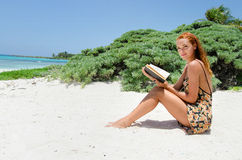 Woman reading at beach Stock Photos