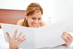 Woman reading on the bed Stock Photos