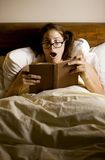 Woman Reading in Bed Stock Photo