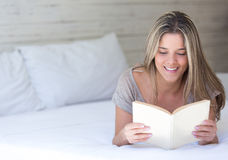 Woman reading in bed Stock Photos
