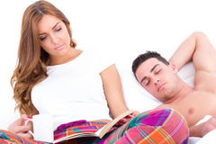 Woman reading in bed with coffee while man is sleeping Royalty Free Stock Images