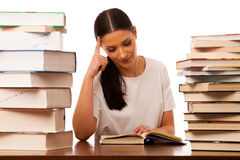 Woman reading behind the table between two pile of books. Woman reading behind the table between two pile of books happy to get new knowledge Royalty Free Stock Photography