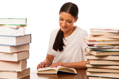 Woman reading behind the table between two pile of books. Woman reading behind the table between two pile of books happy to get new knowledge Stock Photography