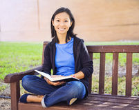 Woman Reading. On a bench outdoor on a sunny day royalty free stock photo
