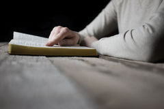 Woman reading the bible in the darkness Stock Photography