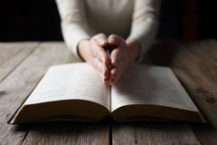 Woman reading the bible in the darkness Stock Photos