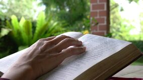 Woman reading the bible in the garden. Fingers turning pages.